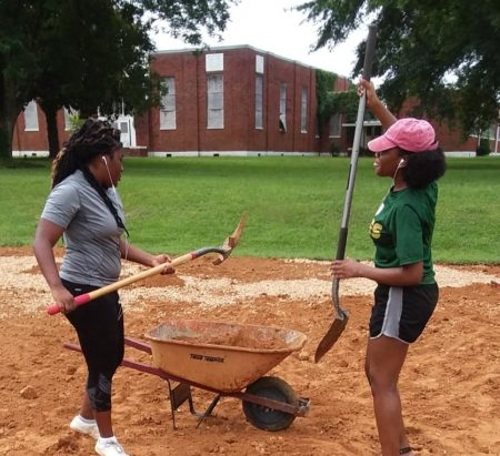Two community volunteers from Duck Hill, MS, shovel dirth into a wheelbarrow.