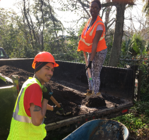 Two workers implement sustainable landscaping in Savannah, Georgia, to create a more sustainable south.
