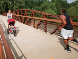 Joggers run across a greenway bridge in a sustainable south.