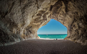 A photo of a cave looking out to a crystal blue ocean and beach for SSDN storytelling program