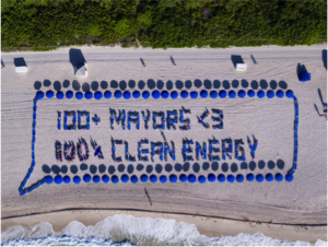 "Aerial image of people standing in a pattern to create the message ""100 Mayors love 100% Clean Energy"""